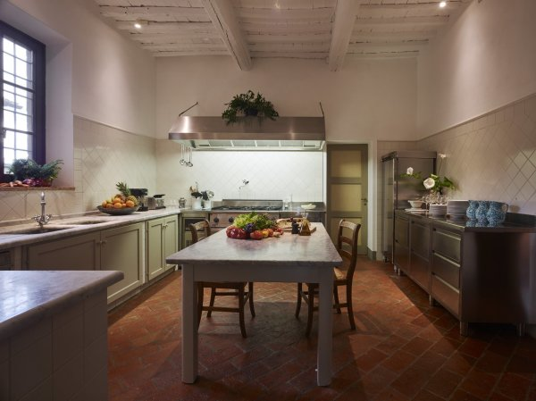 With an antique table and wooden chairs this fully equipped kitchen has a farmhouse look