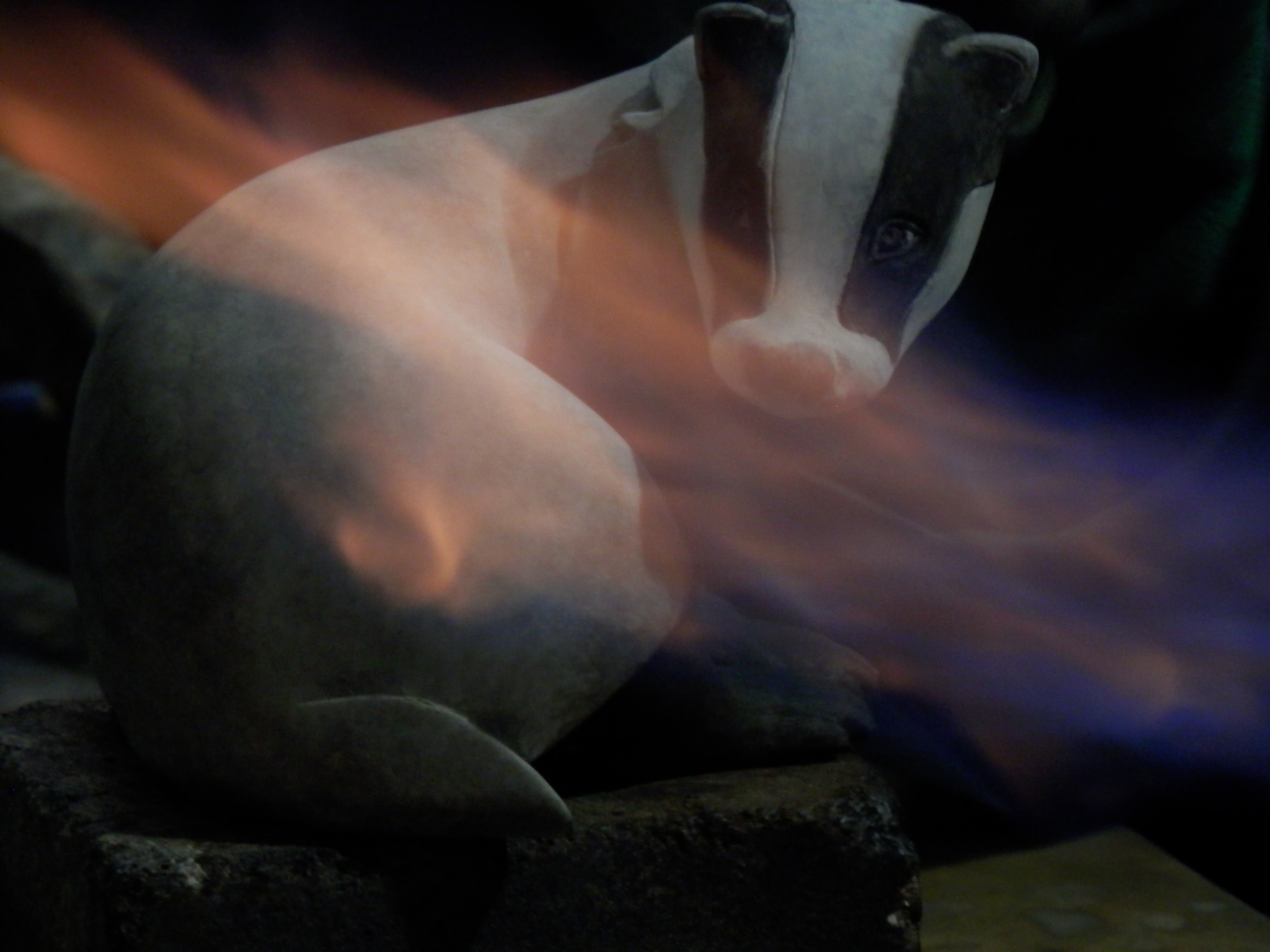 A badger sculpture with the flame of a patination torch caressing its surface.