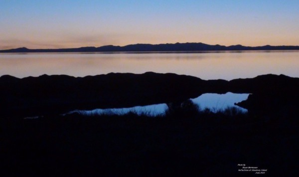 Photo of Great Salt Lake with the reflection of the sky and the rocks and distant mountains, beautifully relaxing evening as life should be.