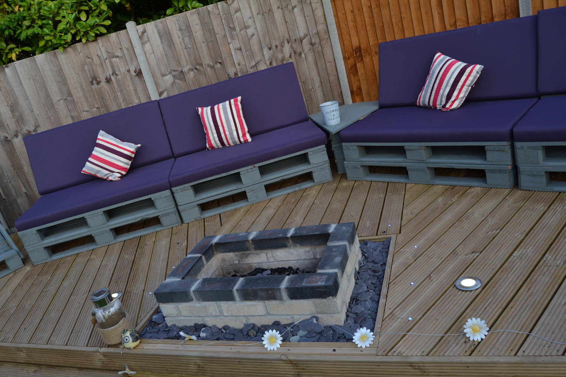 Pallet made garden settee on deck with built in fire pit