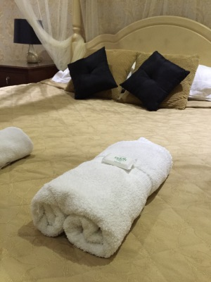 Close up image of double bed with gold linen and black pillows with towel rolled up on top finished with small hotel soap.