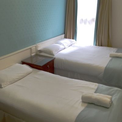 A Double Bed and a Single Bed With White Linen and Duck egg Throws there are Towels folded on the bed and the Decoration is Duck Egg Blue and Gold.
