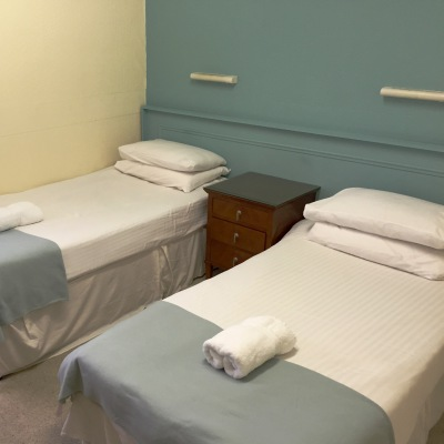 Two Twin Single Beds With White Linen and Duck Egg Coloured Throws there are Two Folded Towels on the Beds and the Decoration is Duck egg Blue and Gold.