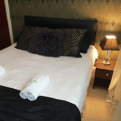 Double Bed With White Linen and Black Pillows and Throw, there are Towels Folded on top of the bed and the Decoration Is Black and Gold.