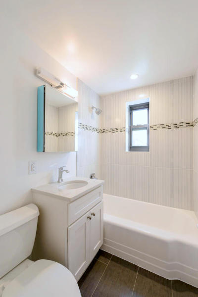 The fully renovated bathroom includes timeless porcelain tiles and a white vanity