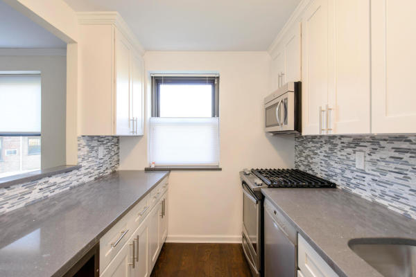 The windowed kitchen includes a dishwasher and wine cooler