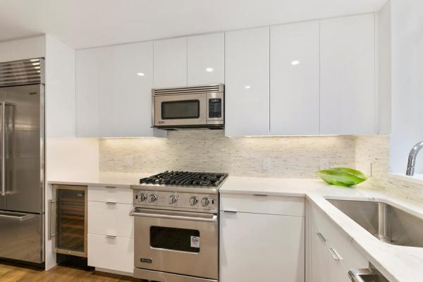 Custom high gloss white kitchen with Viking and Subzero appliances and a wine cooler