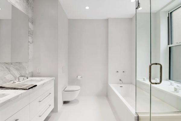 En-suite master bathroom with double vanity, in-floor heating, separate shower and tub, a Marble feauture wall and Waterworks fixtures