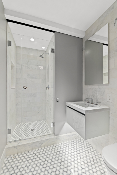"""Guest bathroom featuring a """"secret"""" shower and timeless marble flooring"""