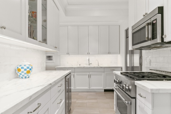 Marble kitchen with a Subzero Fridge, a wine cooler and dishwasher