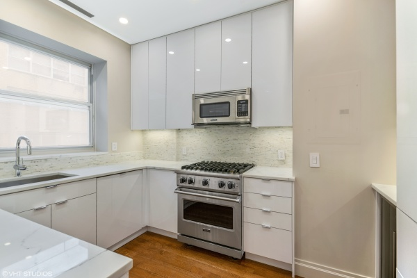 Custom high gloss white kitchen with Subzero and Viking appliances as well as a wine cooler