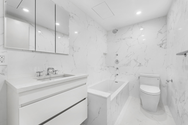 Timeless bathroom with Porcelanosa Marmol Carrara tiles, in-floor heating and Waterworks fixtures