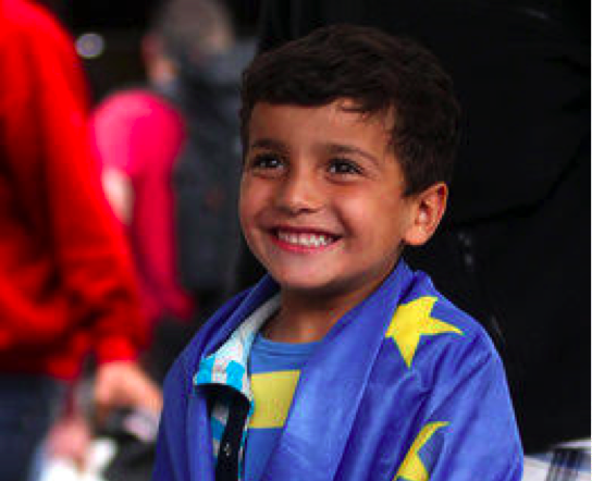 A smiling refugee arriving in Germany (Image via The Huffington Post)