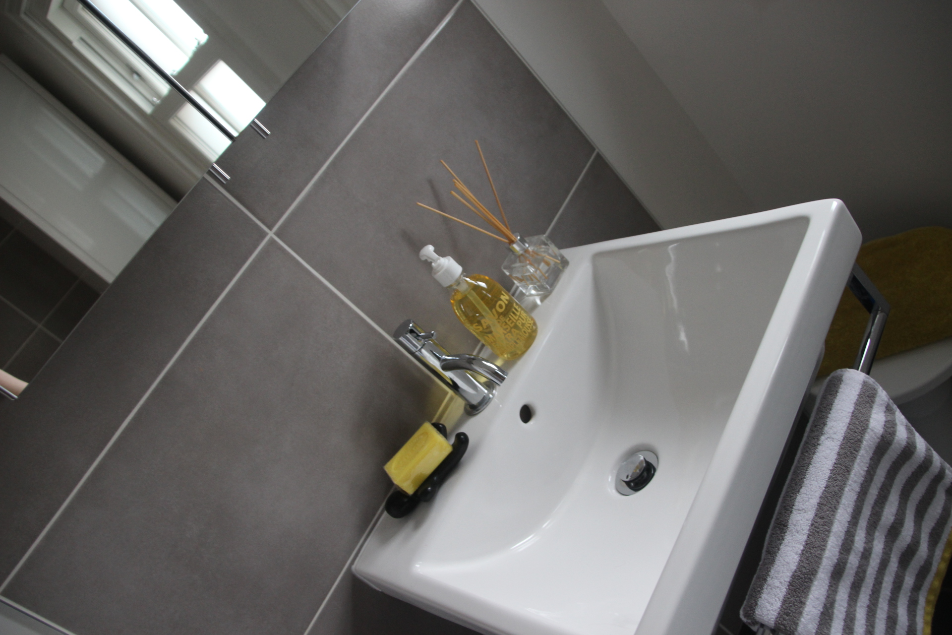 family bathroom; washbasin; stripes; grey; yellow; tiles; white company; towel; scent