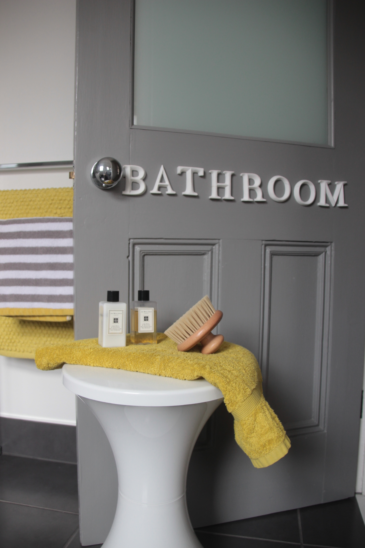 family bathroom; stripes; grey; yellow; tiles; habitat; stool; jo malone; towel; scent