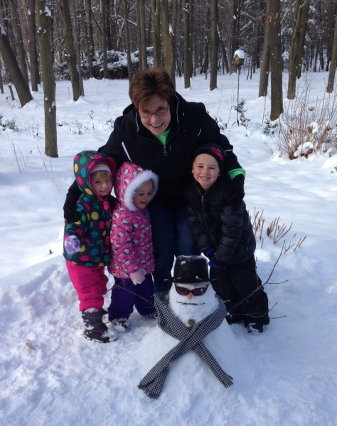 Sandi with her grandchildren, Abigail, Addison and Brody enjoying their friendly snowman named Cool Joe.