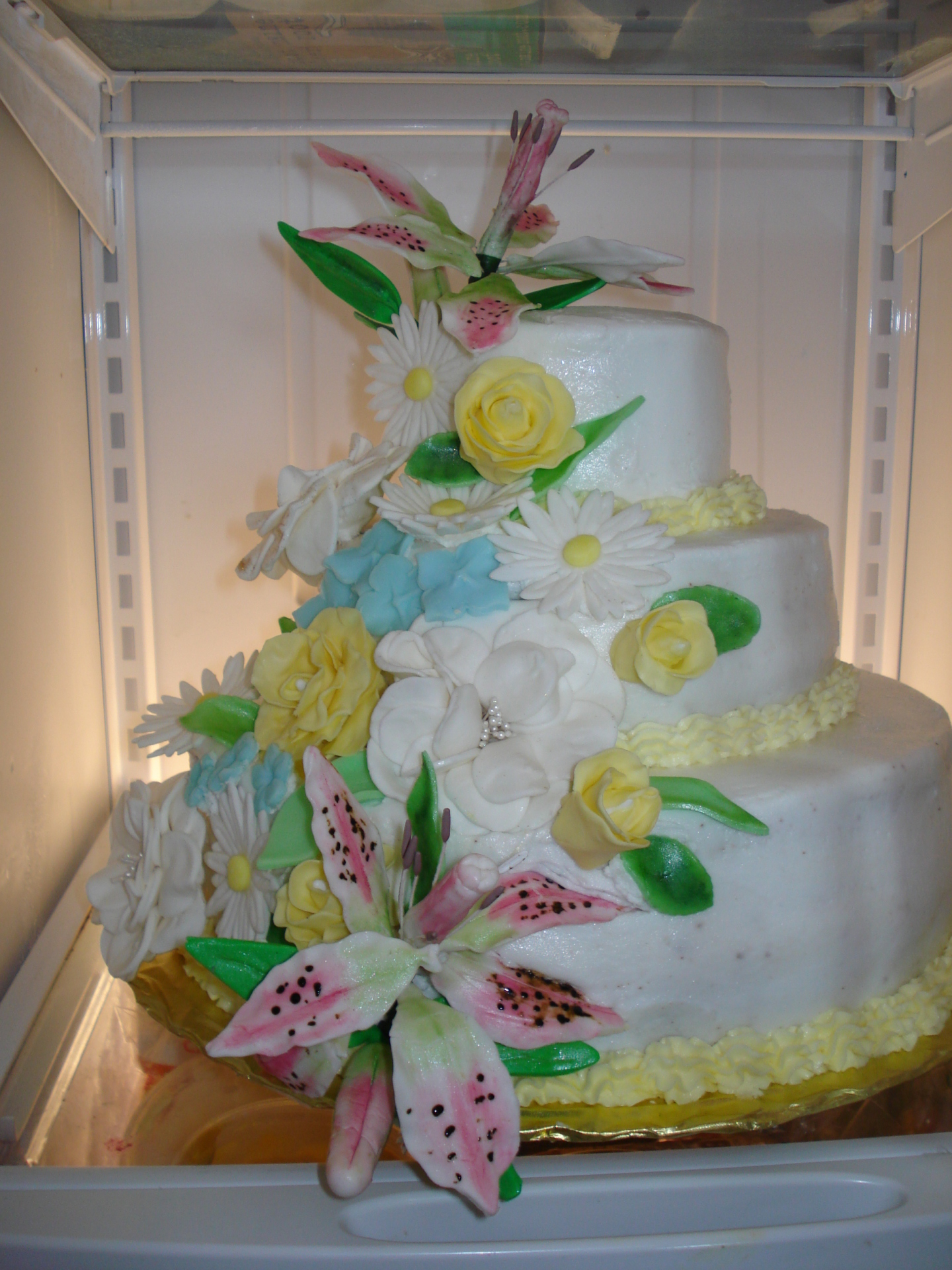3 Tiered Chocolate Cake w/ raspberry filling, white fondant overlay with Spring inspired gum paste hand made flowers