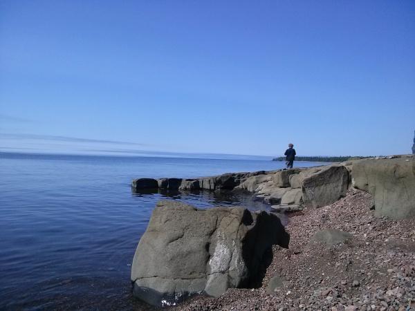 Boy climbing rocks along the North Shore