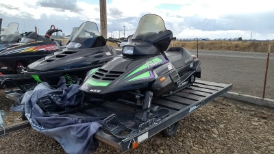 2 Arctic Cat snowmobiles sitting on a black single axel snowmobile trailer