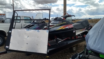 3 Polaris Snowmobiles sitting on a black single axel snowmobile trailer