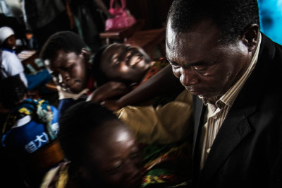 Rwanda, Kibeho. During the prayer in the room of the apparition, a  faithful is seized with convulsions, and considered a victim of demonic possession.