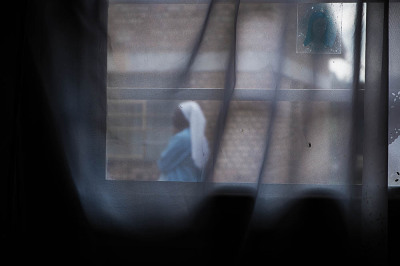 Rwanda, Kibheo. Nun seen trough the window of the apartment of Nathalie Mukamazimpaka, one of the visionaries.