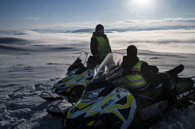 Norway, Finnmark. Anne and Kristine on their snowmobile on the top of a hill, looking for traces of the passage of the reindeer.