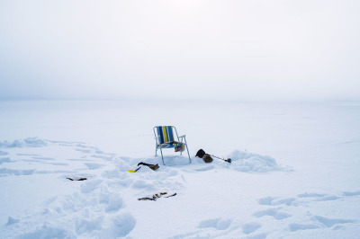 Norway, Finnmark. A chair used to fish in the frozen lake.