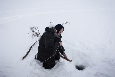 Norway, Finnmark. An old Sami woman fishing.