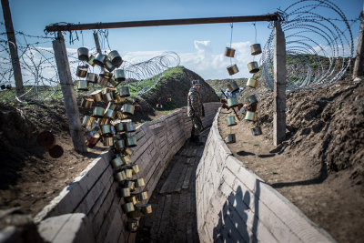 NKR Frontline with Azerbaijan, Agdam area. A soldier is walking into the trenches. Cans and barbed wires are use to alarm in case of an Azeri saboteurs entry.