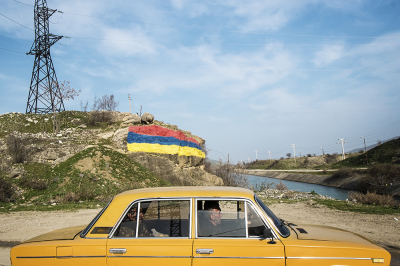 Madagis Village, Martakert region. NKR. Ziguli in front of an armenian flag painted on a rock at the entrance of the village.