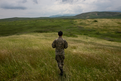 NKR Frontline with Azerbaijan, Hadrut region. A Young soldier is walking on a field on the frontline during a break of the fightings.