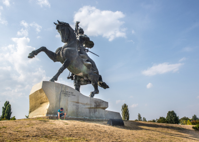 Tiraspol, Pridnestrovie. A young boy is playing with a mobile phone under the Alexander Suvorov monument in the city center. Suvorov was the founder of the city in 1792.