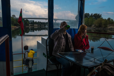 "Tiraspol, Pridnestrovie. Families on the turistic sunday boat on the Dnepr river are making a round trip from Tiraspol to Bender. The river is one of the major rivers of Europe (fourth by length). Pridnestrovie's name literally means ""beyond the River Dnepr"". Along its shores has been fought the heaviest fights during the independence war in 1992 because the river itself represented a natural border between the Russian an Moldavian population."