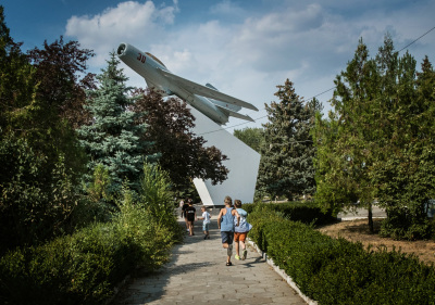 Tiraspol, Pridnestrovie. Young boys are running under the airplane monument to military pilots in the Victory park.