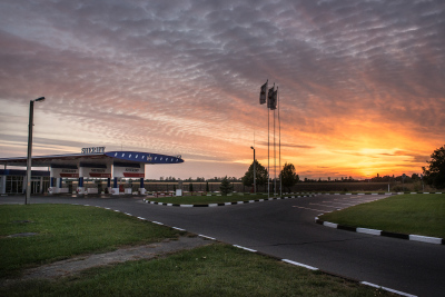 Tiraspol, Pridnestrovie. Sunset on a Sheriff gasoline station. Basically, during the last years, Transnistrian government policies have isolated the region from the rest of Moldova, allowing Sheriff to forge a monopoly there. Formed in the early 1990s by Viktor Gushan and Ilya Kazmaly, former members of the special services, now has also the son of the president in the board. Sheriff has grown to include nearly all forms of profitable private business in the country and has even become significantly involved in Transnistrian politics and Soccer. In fact, Sheriff owns a chain of petrol stations, a chain of supermarkets, a TV channel, a publishing house, a construction company, a Mercedes-Benz dealer, an advertising agency, a spirits factory, two bread factories, a mobile phone network, the football club FC Sheriff Tiraspol and its newly built Sheriff Stadium at an estimated cost of $200 million including a five-star hotel still under construction.