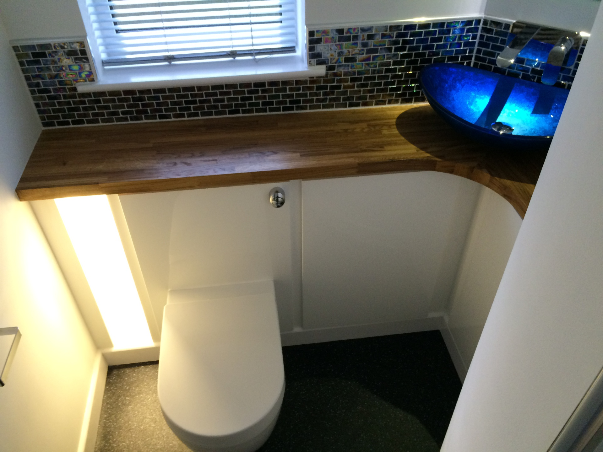 Concealed cistern toilet with custom made high gloss white cabinets