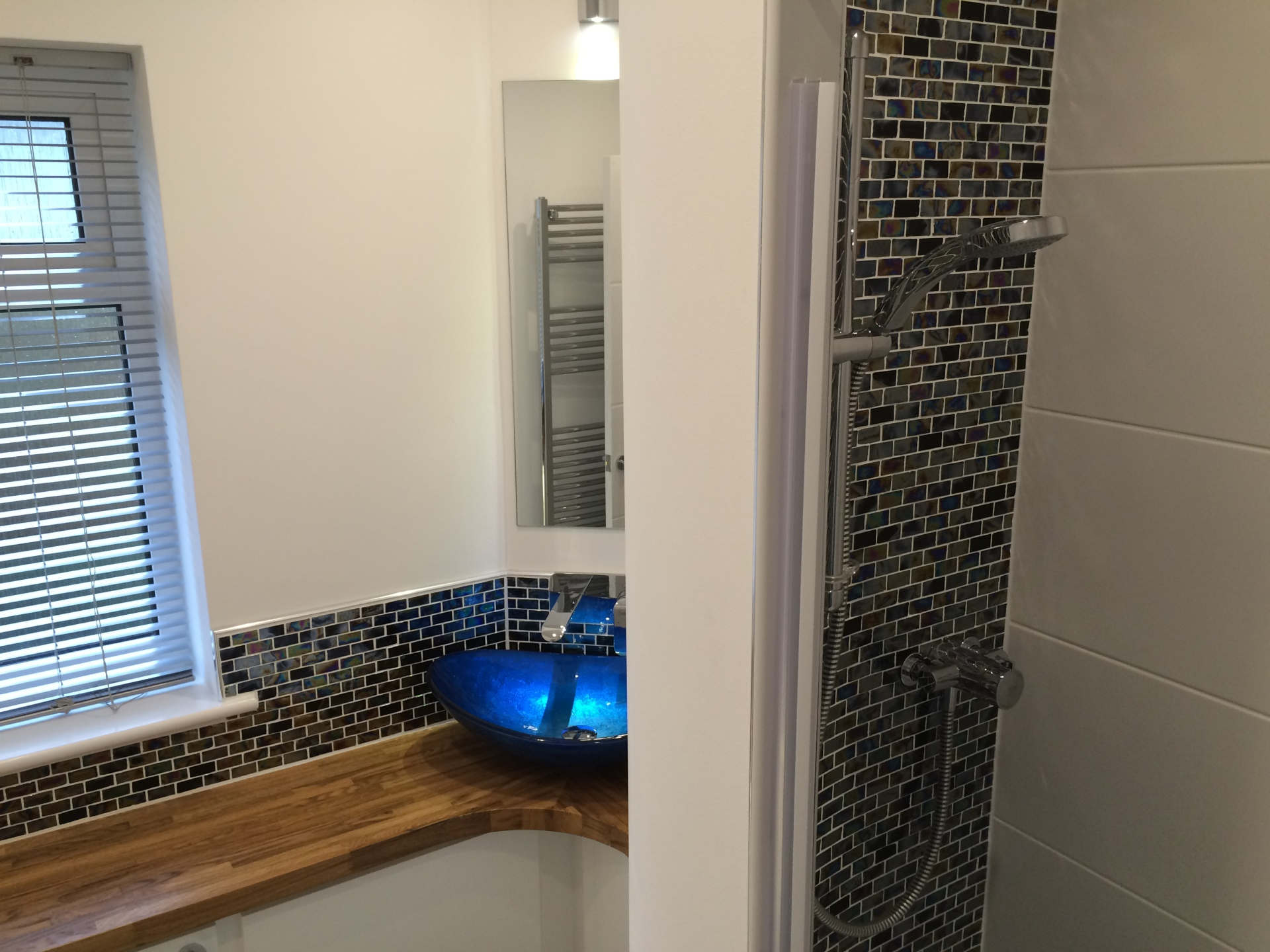 White painted bathroom with blue glass sink and oily glass mosaic tiles