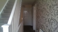 decorated staircase with wallpaper feature wall