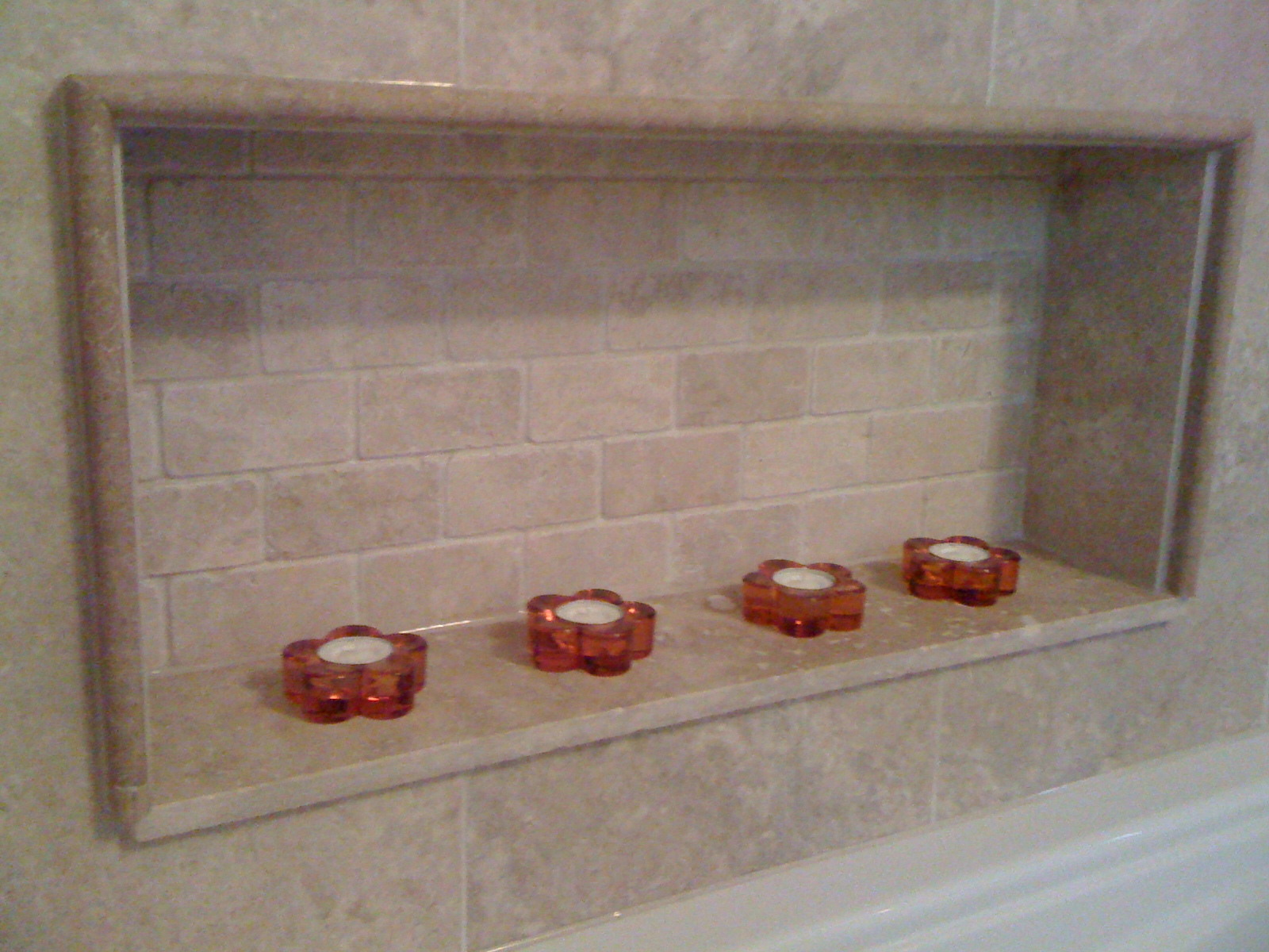 Bathtub inlet tiled in travertine with back splash