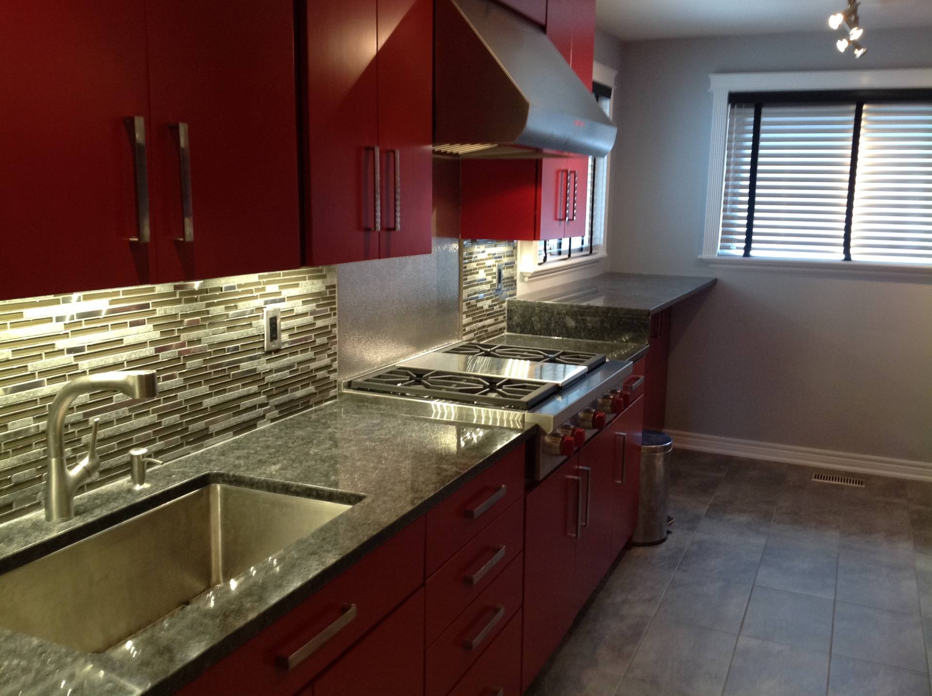 Kitchen painted in red with Gas top stove and Stainless steel range hood
