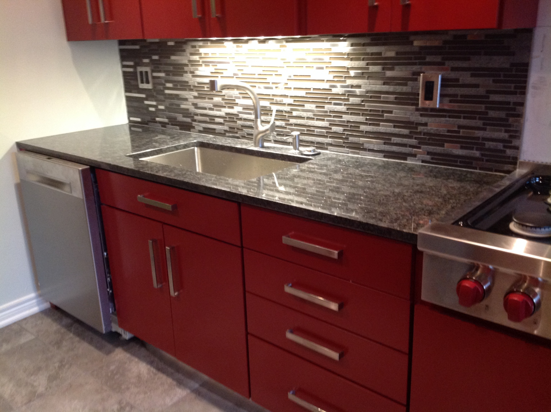 Red Gloss Kitchen with granite and marble/steel backsplash