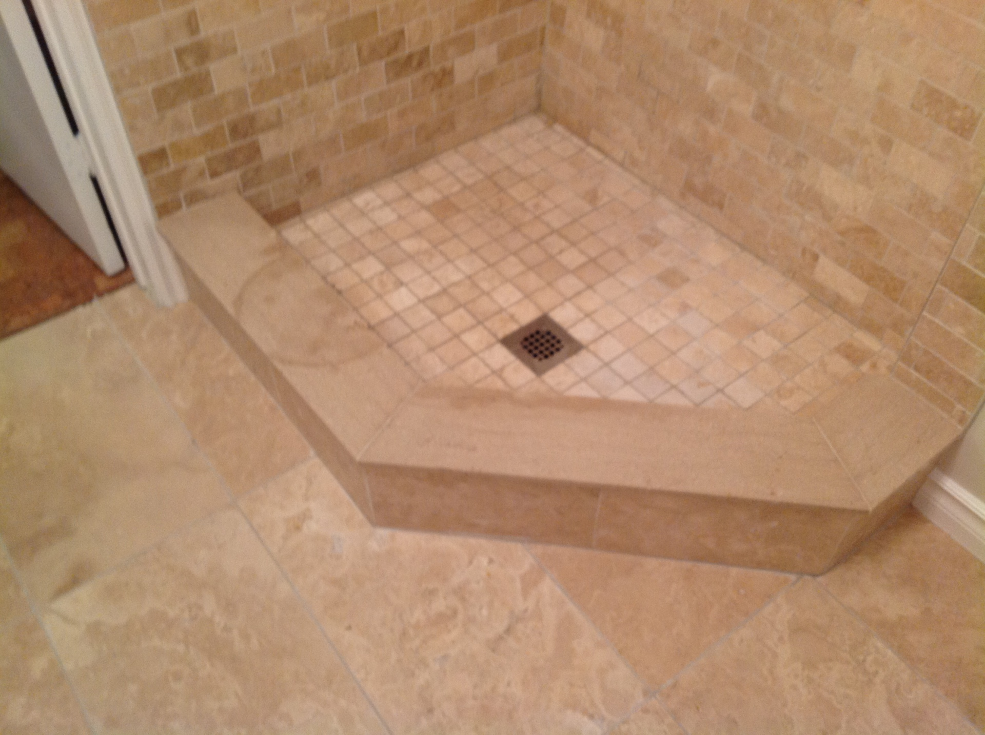 Custom stand up shower done with travertine mosaic and stone sills