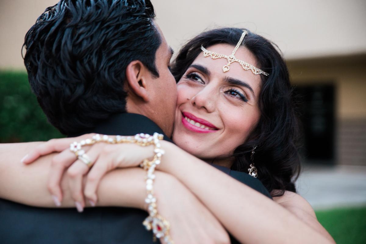 bride hugging groom smiling outdoor portrait