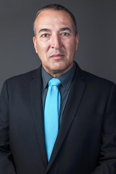 indoor headshot black background man blue tie suit