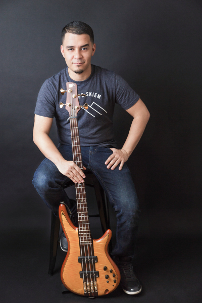 indoor headshot low key black background orange bass sitting