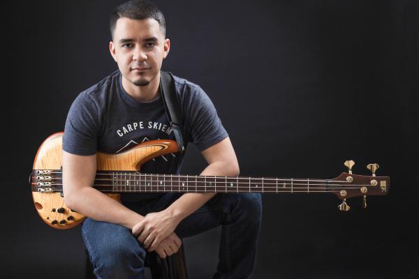 indoor headshot low key black background holding orange yellow bass sitting