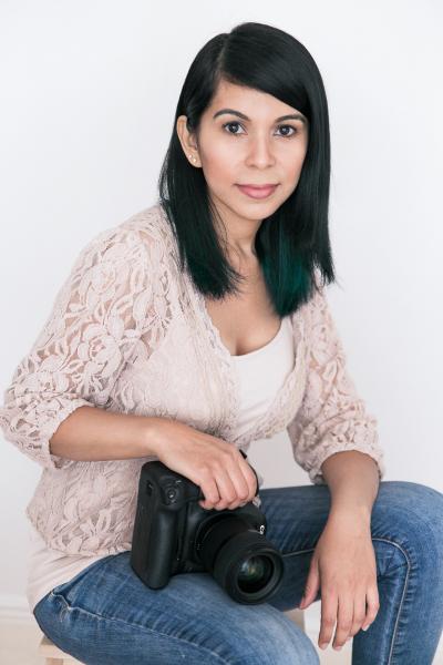 indoor headshot photographer holding camera to eye white background