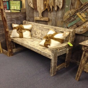 This distressed wood bench made from reclaimed wood are set off with these pillows. Don't miss the old wood doors in the back.