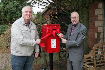 Monks' Muir Community Association Chairman Jim Herron and George unvail post box